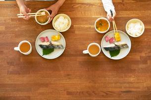 テーブルの上でごはんを食べる男の子の手の写真素材 [FYI01803198]