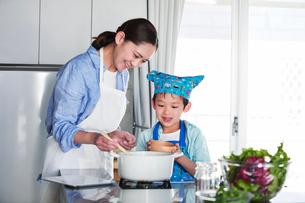 キッチンで料理を作る男の子と女性の写真素材 [FYI01803201]