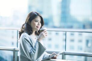 カフェでコーヒーカップとタブレットPCを持つ女性の写真素材 [FYI01803209]