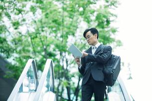 タブレットPCを持ちエスカレーターに乗るビジネスマンの写真素材 [FYI01803220]
