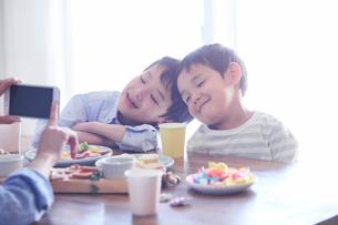 料理を食べる男の子をスマートフォンで撮影する女性の写真素材 [FYI01803229]