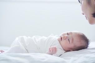 寝る赤ちゃんと見守る母親の写真素材 [FYI01803249]