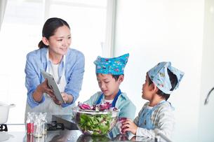 キッチンで料理を作る男の子と女性の写真素材 [FYI01803253]