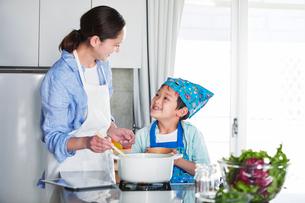 キッチンで料理を作る男の子と女性の写真素材 [FYI01803262]