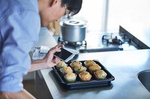 キッチンに立ちスマートフォンでマフィンの写真を撮る男性の写真素材 [FYI01803265]
