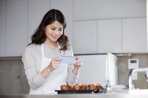キッチンに立ち写真を撮る女性の写真素材 [FYI01803297]