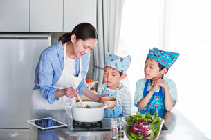 キッチンで料理を作る男の子と女性の写真素材 [FYI01803305]