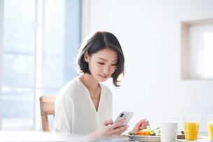 スマートフォンをみる女性の写真素材 [FYI01803321]