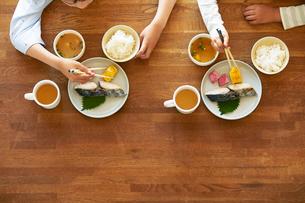 テーブルの上でごはんを食べる男の子の手の写真素材 [FYI01803322]