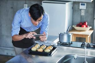 キッチンに立ちスマートフォンでマフィンの写真を撮る男性の写真素材 [FYI01803331]