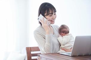 ノートパソコンを見る女性と赤ちゃんの写真素材 [FYI01803338]