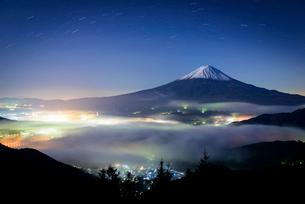 新道峠より望む富士山と街明かりに照らされる雲海の写真素材 [FYI01803344]