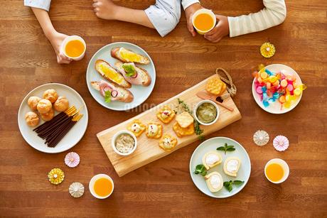 テーブルに並ぶパーティ料理と人の手の写真素材 [FYI01803356]