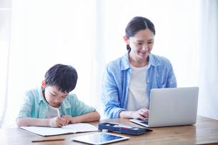 ペンを持つ男の子とパソコンを見る母親の写真素材 [FYI01803374]