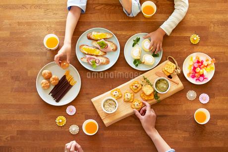 テーブルに並ぶパーティ料理と人の手の写真素材 [FYI01803383]