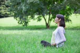 緑の中でヨガをする女性の写真素材 [FYI01803387]