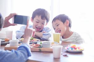 料理を食べる男の子をスマートフォンで撮影する女性の写真素材 [FYI01803427]