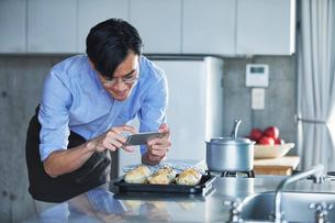 キッチンに立ちスマートフォンでマフィンの写真を撮る男性の写真素材 [FYI01803430]