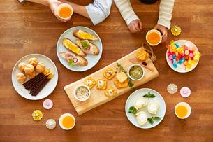 テーブルに並ぶパーティ料理と人の手の写真素材 [FYI01803450]