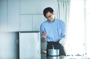 キッチンに立ち料理を作る男性の写真素材 [FYI01803517]