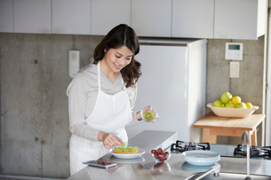 スマートフォンを見ながらケーキを作る女性の写真素材 [FYI01803538]