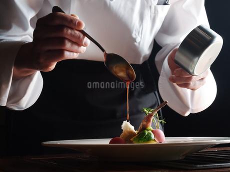 洋食 調理風景 ソースかけの写真素材 [FYI01805549]