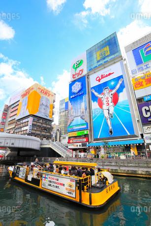 大阪道頓堀の商業ビルと川を遊覧するとんぼりリバークルーズの写真素材 [FYI01805573]