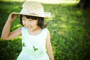 帽子をおさえる女の子の写真素材 [FYI01806701]
