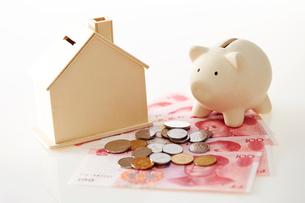 豚の貯金箱と家の模型の写真素材 [FYI01807457]