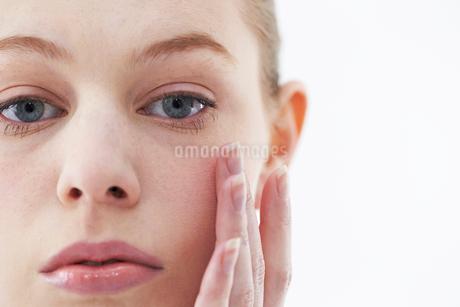 顔に手を当てる女性の写真素材 [FYI01809022]