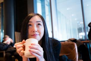 カフェでくつろぎ上を見る女性の写真素材 [FYI01810385]