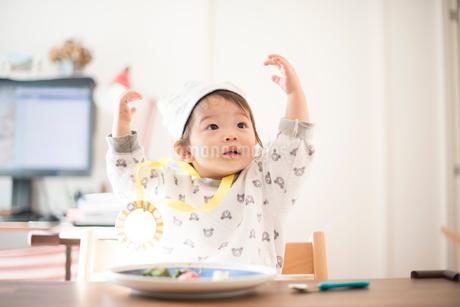 食事中にバンザイして上を見る誕生日の子供の写真素材 [FYI01810402]
