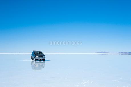 ウユニ塩湖と鏡張の水面を走る車の写真素材 [FYI01810617]