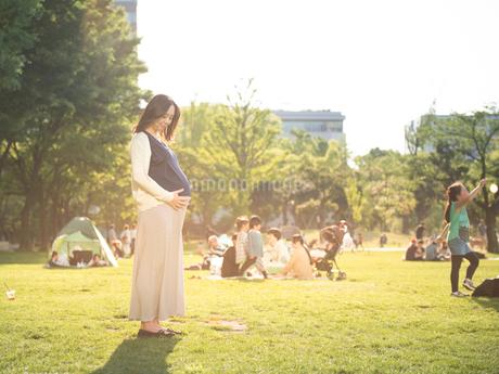公園でお腹をさする臨月の女性の写真素材 [FYI01810651]