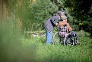 車椅子を押すシニア夫婦の写真素材 [FYI01812561]