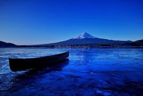 氷結した河口湖より望む富士山と氷に浮かぶカヌーの写真素材 [FYI01814299]