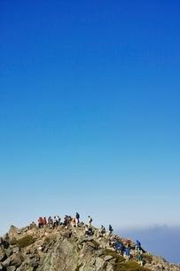 おおぜいの登山者が登る乗鞍高原の魔王岳山頂の写真素材 [FYI01814515]