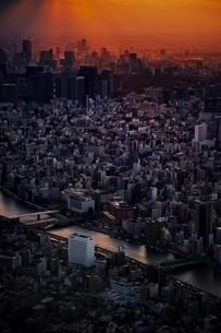雲間から光の筋が注ぐ高層ビル群の写真素材 [FYI01814542]
