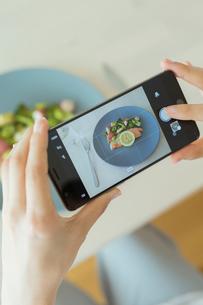 食事をスマートフォンで撮影する女性の写真素材 [FYI01814574]