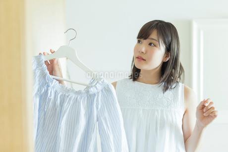 クローゼットから服を取り出す女性の写真素材 [FYI01814583]