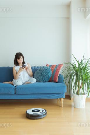 部屋でくつろぐ女性とお掃除ロボットの写真素材 [FYI01814619]