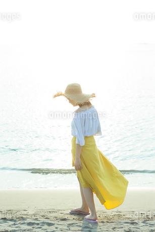 浜辺を歩く女性の写真素材 [FYI01814751]