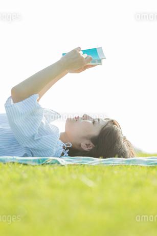 横になり本を読む女性の写真素材 [FYI01814755]
