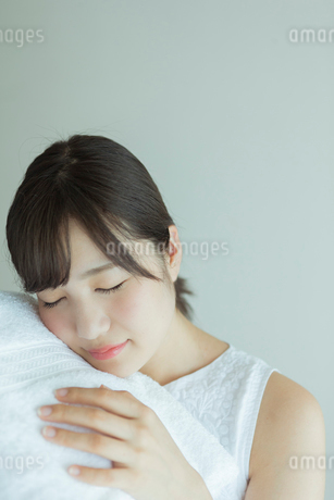 タオルに顔を埋める20代女性の写真素材 [FYI01814803]