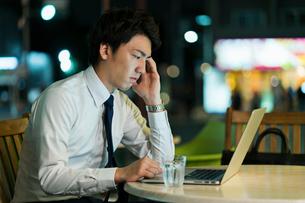 テラスで残業をするビジネスマンの写真素材 [FYI01814889]