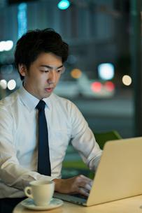 テラスで残業をするビジネスマンの写真素材 [FYI01814902]