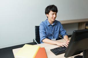 笑顔で仕事をする20代ビジネスマンの写真素材 [FYI01814912]