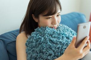 ソファーに座りスマートフォンを操作する女性の写真素材 [FYI01814932]