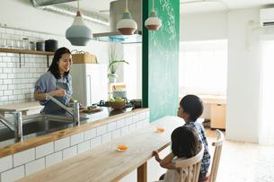 料理をする女性と会話する子供達の写真素材 [FYI01814984]