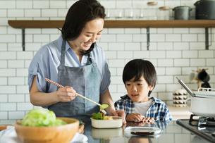 キッチンでお弁当作りをする女性と寄り添う男の子の写真素材 [FYI01814998]